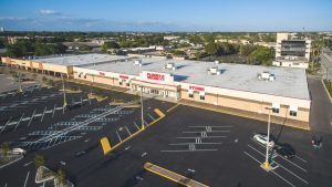 """An aerial image of a white and tan commercial building called, """"Floor & Decor"""" with a flat roof and completed waterproofing."""