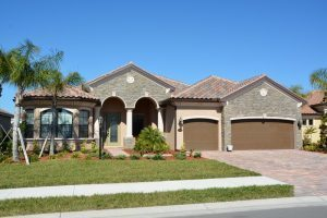 A residential tile roof on a tan home done by the local roofing company in Fort Myers, FL.