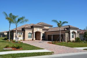 A residential tile roof on a tan home done by the local roofing company in Sarasota, FL.