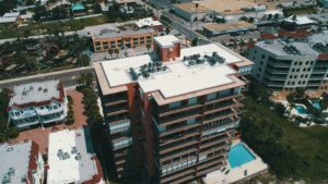 An image of the red commercial condo building in a business lot in Madeira Beach Condos on the beach. The local roofing and waterproofing company contractors applied corrugated asphalt roofing to the building.