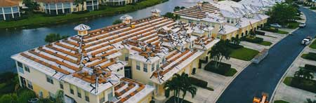 The aerial view of a residential home in Pompano Beach, Florida surrounded by grass. The local Pompano Beach roofing company installed red clay tile.