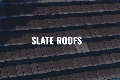 """The image of a commercial buildings' black slate roof with the caption, """"Slate Roofs"""""""