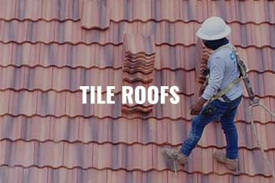 """A Crown Residential Roofing contractor on a residential home carried red tiles on the tiled roof to replace the roof. The caption reads, """"Tile Roofs"""""""