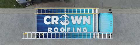 The aerial view of the Crown Roofing Truck with a blue and white Crown Roofing logo on the roof.